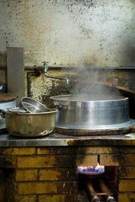 カウンターの右手にある煉瓦造りのかまど。強火で複数の羽釜を煮込んでいる