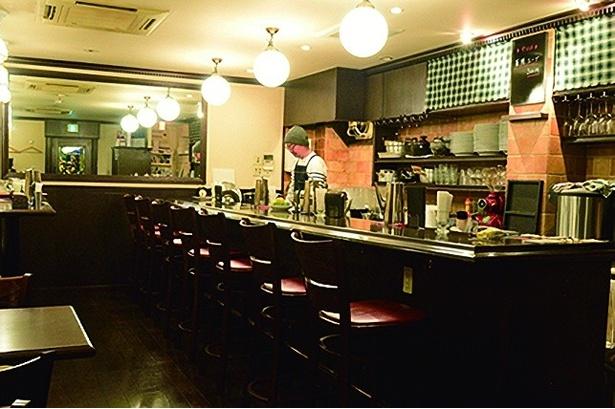 白×黒を基調とし、落ち着いた雰囲気が心地良い店内。カウンターの後ろに一段高く設置されたソファー席があり、カレーが出てくるまでキッチンの様子が楽しめる