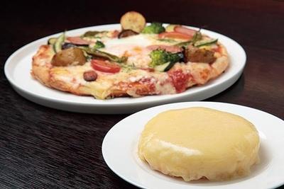 塩けのあるオリジナルチーズを使った「デンマークチーズケーキ」(手前・378円)。「ピザ(カプリチョーザ)」(奥・1425円)には、旬の野菜を豊富に使用/REAL DINING CAFE