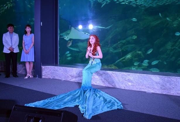 【写真を見る】アリエル役の谷原志音が舞台衣装で登場。外洋大水槽を背景に、劇中歌「パート・オブ・ユア・ワールド」を披露した