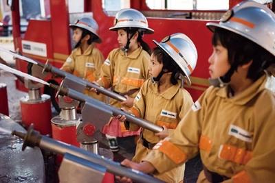 消防士として防火服とヘルメットを身に着け、火災が発生すると、本物そっくりの消防車に乗って火災現場へ。実際に水が出る放水銃が使えるとあり、子供たちも大興奮/キッザニア甲子園