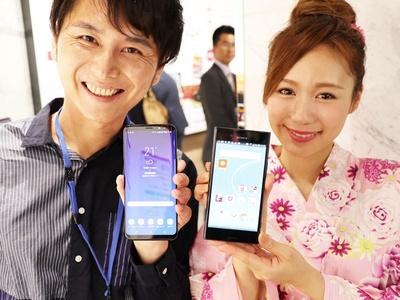 伊藤の持つスマホがGalaxy S8+(写真左)、女性モデルの持つスマホがXperia XZ Premium(写真右)