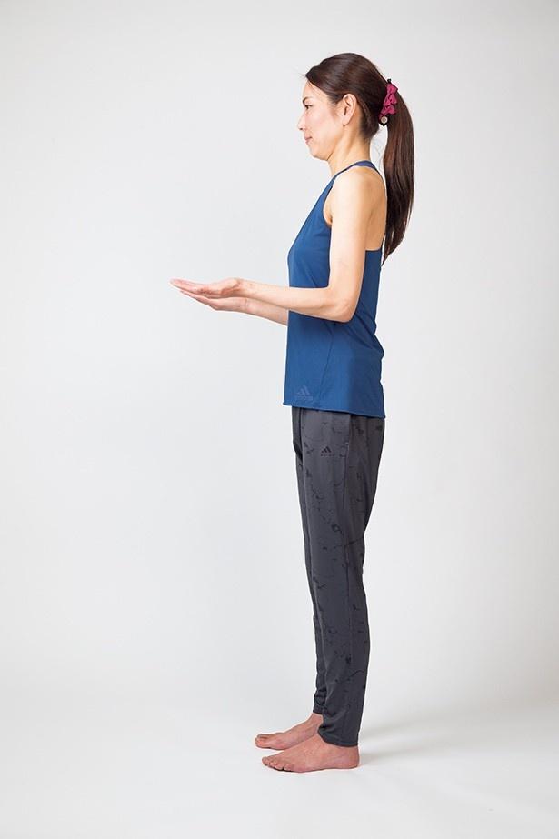 【写真を見る】正しい姿勢のつくり方1:壁に体の後ろ側をつけてまっすぐに立ち、ひじを90度に曲げて手を前に出す
