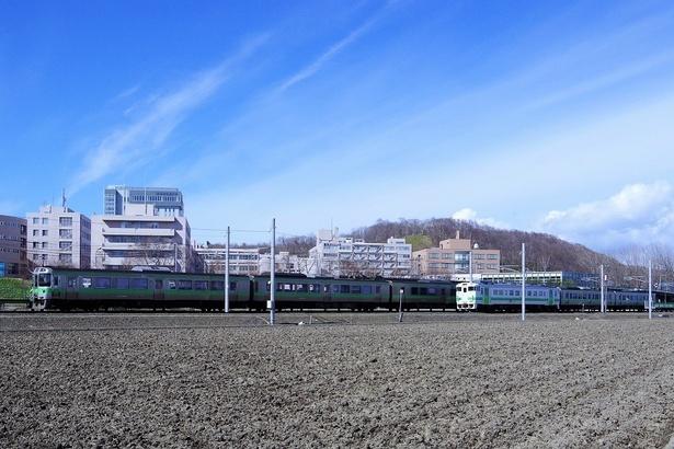 【写真で見る】北海道医療大学駅に停車中の通勤形電車と、隣を通り抜ける1両のディーゼル列車(撮影:北海道医療大学駅付近)