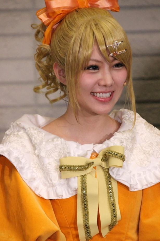マスコミ質問に明るい笑顔で答える田中。金髪のカツラが似合い過ぎ!