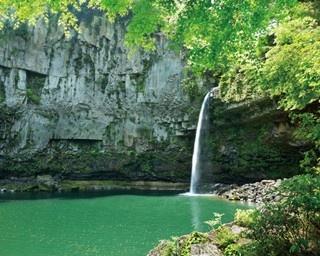 山の中にぽっかりと空いた滝つぼ。エメラルドグリーンに輝く神秘的な光景だ