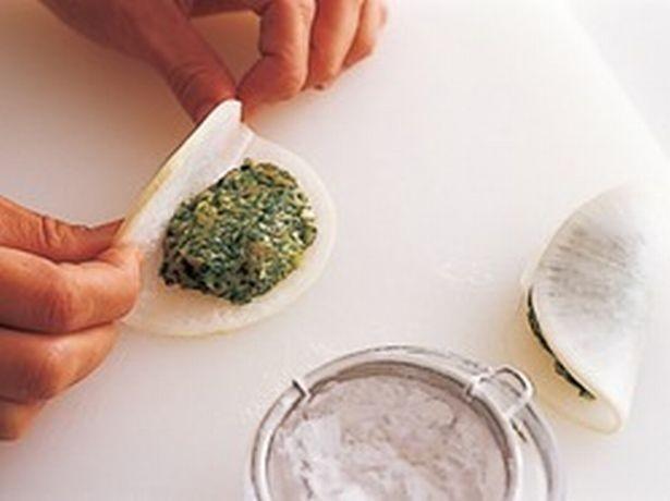片栗粉を薄くふったところに、ひき肉だねをのせて、半分に折りたたむ。片栗粉をふっておくと、ひき肉だねがはがれにくくなる