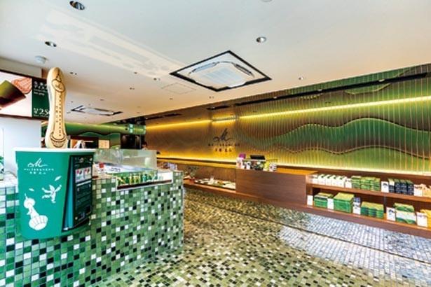 濃淡のある信楽焼の、緑のタイルをあしらった店内。無料サービスのコーヒーマシンを備える/マールブランシュ 京都タワーサンド店