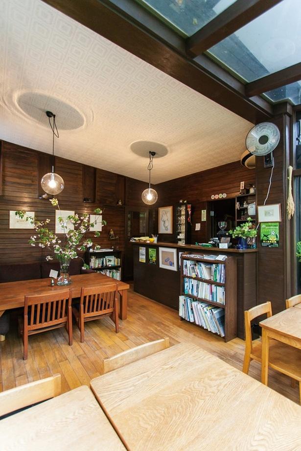 「cafe kaeru」の店内。ガラス張りになった窓際の席からは、緑いっぱいの庭園も眺められる
