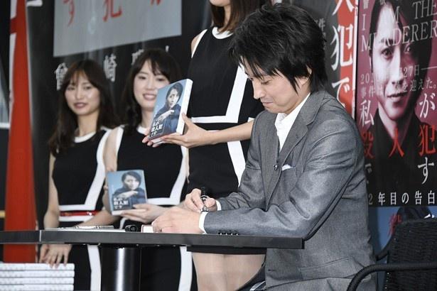【写真を見る】藤原の提案で会場のお客さん全員に自腹でサイン本をプレゼント