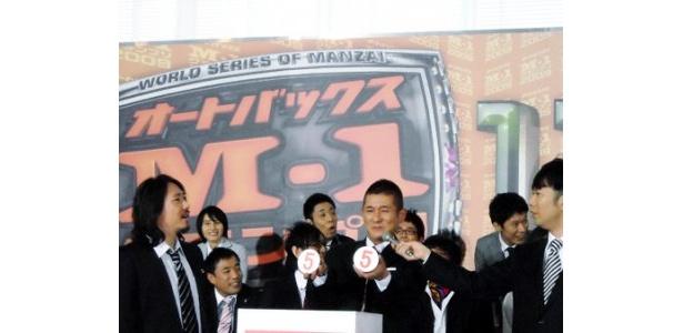 笑い飯・哲夫(写真右)は、腕にはめたパワーストーンに願いを込めて恐る恐るクジを引いて5番に