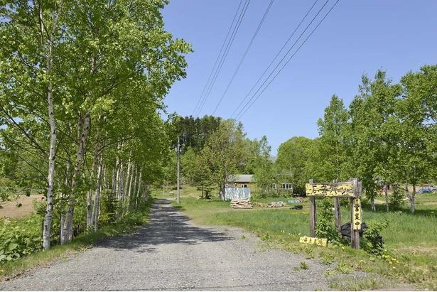 「奥土農場 石窯パン工房」はこの道を進んだ先にある、黄色い二階建ての建物