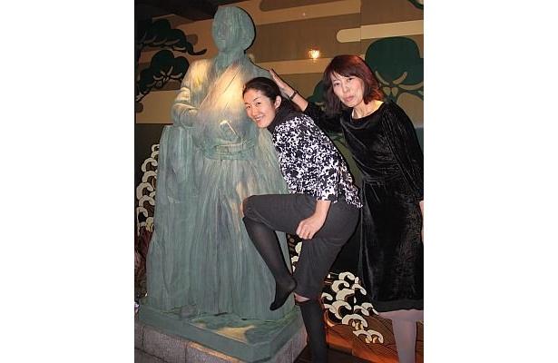 「龍馬邸」のエントランスにある龍馬像で記念撮影をする客たち。龍馬の身長ってこんなに高いんだと驚く