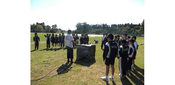 鉄を変形しやすくするため、バーナーの炎を当てる橋本先生(中央左)