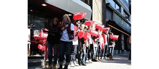 赤い風船を配るモデルたちの姿も