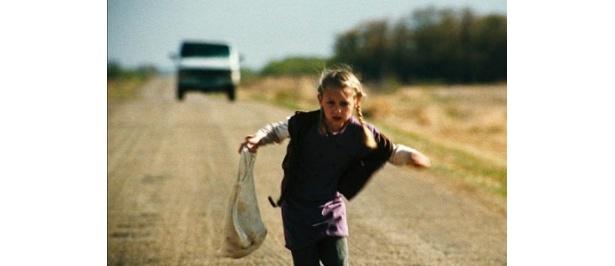 必死に逃走する少女。その背後に一台の車が迫り寄る…