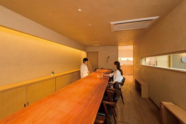 「Zelkova Coffee」の店内1F。漆喰の壁に一枚板のカウンターが映える