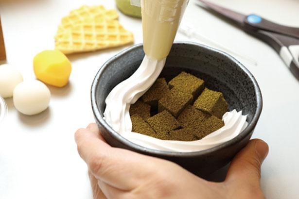 クリームを絞り、塩化ビニール樹脂製の具材をデコレート/でざいんぽけっと 京都タワーサンド店