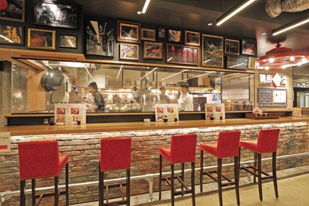 オープンキッチンを囲むように、真っ赤な椅子のカウンター席を設置/魏飯吉堂