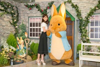【写真を見る】ピーターラビットと一緒にポーズを決める小倉優子。会場入り口にはビアトリクスが愛した、ヒルトップ農場の庭を一部再現