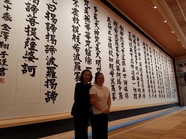 奉納された作品とともに、笑顔でたたずむ金澤翔子氏と母親の泰子氏