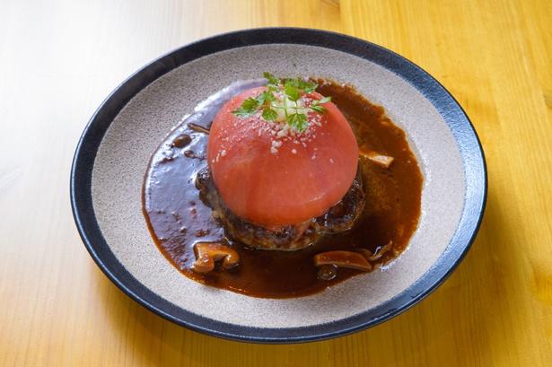 【写真を見る】トマトが丸ごと1個のる「トマトのせハンバーグ」(1220円)。トマトの酸味とクリーミーなデミグラスソースとの相性は抜群