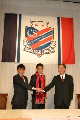 コンサドーレ札幌のタオルマフラーを首から下げ、HFCの矢萩竹美社長(右)、三上大勝強化部長(左)と握手