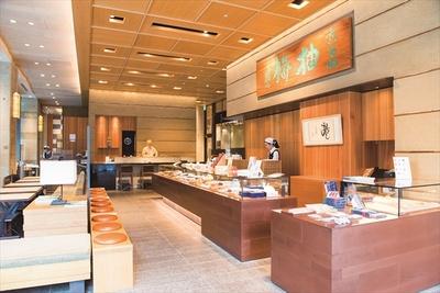 店内には富岡鉄斎の揮毫による「柚餅」の看板が。内装は京都を思わせる素材で造られており、天井やランプには和紙、壁には陶器で直線が描かれ、数寄屋建築風に表現されている