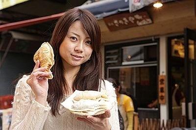 「築地さのきや」のまぐろ焼きを手にする芹沢さん。寿司や海鮮丼以外のおいしい物があるのも築地市場の魅力だ