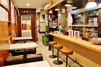 低めで腰かけやすいテーブル席とカウンター。壁には著名人のサインや写真がびっしり