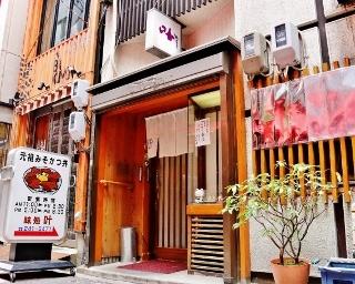 繁華街の路地裏に佇む創業68年の老舗。丼のイラスト看板が目印だ