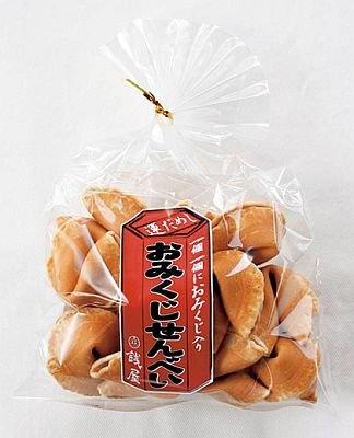 「銭屋」のおみくじせんべい(350円)。半月形で味噌風味のせんべいを割ると、中からおみくじがペロンと登場