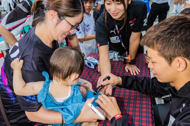 キッズウォークで子供の服にサインをするフォーラムエンジニアリング ADVAN GT-Rの佐々木 大樹選手
