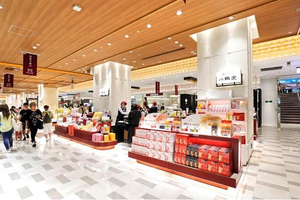 【写真を見る】博多駅マイング「和菓子通り」に位置。二鶴堂で販売する全種類のお菓子がズラリ