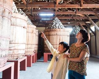 味噌を熟成させる熟成蔵。巨大な味噌樽がズラリと並び、圧巻の迫力だ