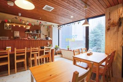 エレベーターから直結。パステル調の壁と明るい木目のぬくもりある空間が印象的/TONTON CAFE