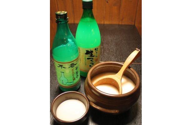 マッコリはかめに入ったものをひしゃくで大き目の器に入れて飲むのが一般的。ボトルは韓国の生マッコリ/「韓国創作料理 マッコリバー てじまぅる新宿店」