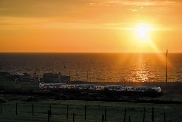 日本海に沈む夕陽を前に、カラフルな車体の「きらきらうえつ」が走っていく