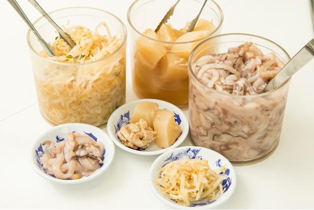イカの塩辛はじめ、煮ダイコン、モヤシなどが無料総菜として卓上に置いてある