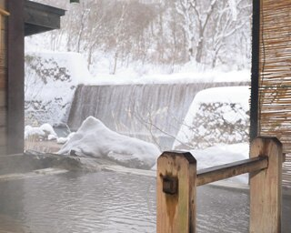 間近に滝が流れる「妙乃湯」の貸切露天風呂。混浴露天はバスタオルの着用も可
