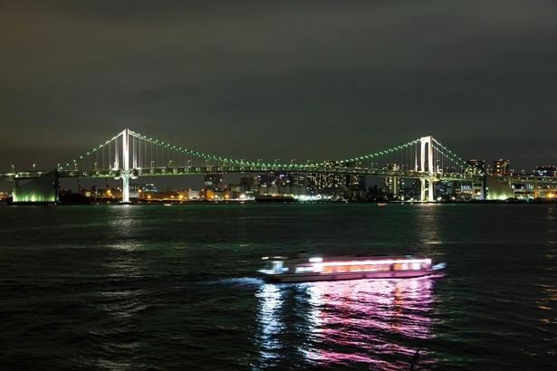 【写真を見る】漆黒の水面に映るレインボーブリッジと船の光