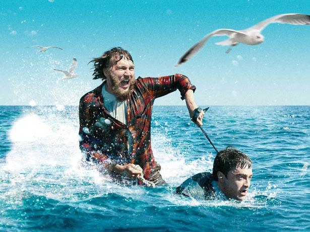 死体のメニ―(ダニエル・ラドクリフ)をジェットスキーにして海を疾走するハンク(ポール・ダノ)
