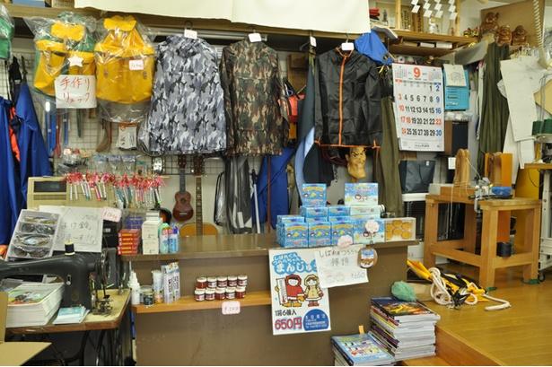 店内はテント屋か釣り具店の様相ですが、カウンターの上にはまんじゅうとせんべいがディスプレイされています