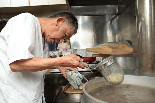 大きな湯で窯を前に。「昔はたくさんの麺を一気に茹でてたんだ」と優しく教えてくれた