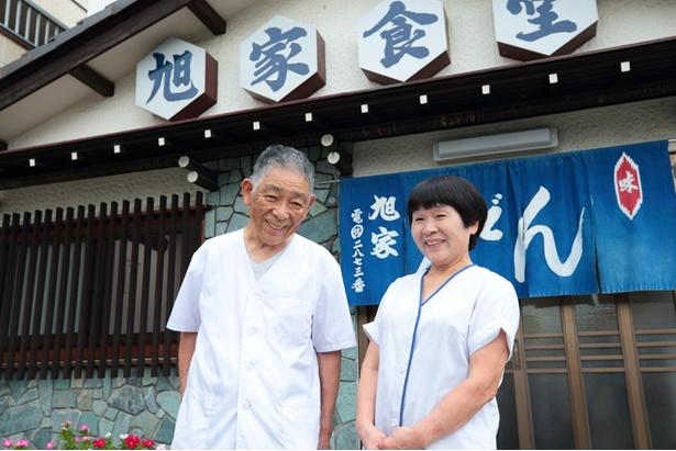 店の前で笑顔を見せる小栗夫婦。康弘さん(左)と、妙子(右)さん