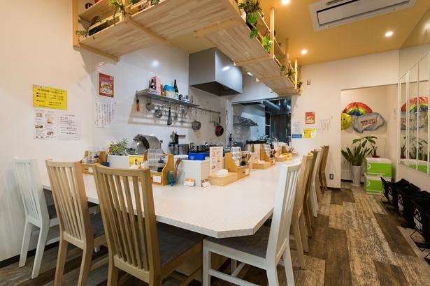 壁だけでなく、カウンターや椅子までも白くし、明るくフェミニンな印象の店内/麺物語 つなぐ