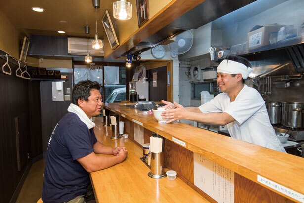 オリジナルの豚骨魚介ラーメ ンを師匠に差し出す橋本さん。まさに緊張の一瞬!