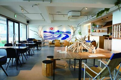 「海沿いの キコリ食堂」の店内奥、真っ白な壁一面に描かれているのは、テラス席から見える材木座海岸越しの江の島の風景