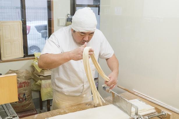 【写真を見る】1日6時間は製麺室で過ごすという胸元さん。自慢の麺は、前日に生地を作り1日寝かせたあとカットする