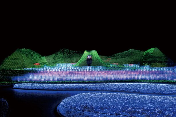 【写真を見る】阿蘇五岳を背景にくまモンがごあいさつ